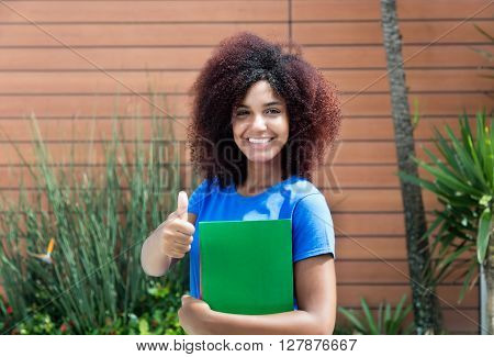 Latin female student in blue shirt showing thumb outdoor with plants in the background ** Note: Soft Focus at 100%, best at smaller sizes