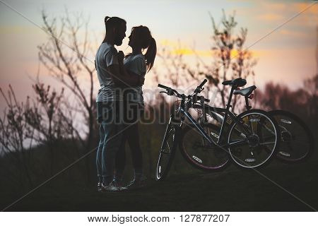 Beautiful Young Loving Couple Hugging At Sunset, There Are Two Bikes. The Concept Of Happiness, Peac
