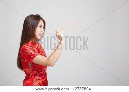 Asian Girl In Chinese Cheongsam Dress With  Chopsticks