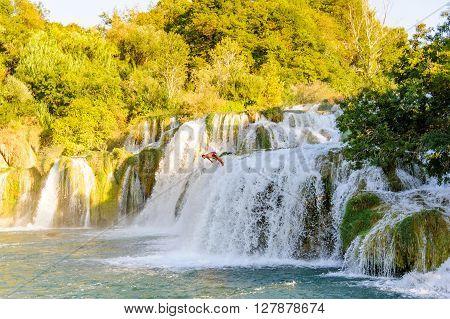 KRKA NATIONAL PARK CROATIA - SEPTEMBER 2 2009: Man caught mid-air diving off the Skradinski Buk waterfalls into the Krka river.