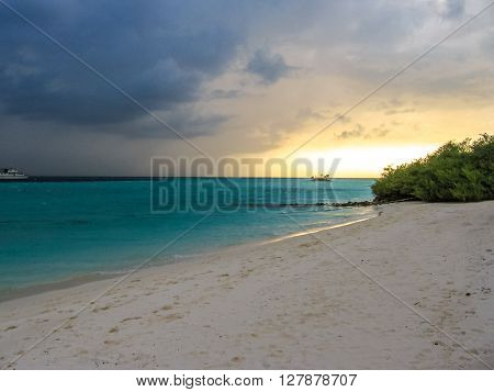 Maldives background. Sunset over the tropical sea and coral beach with colorful clouds in the sky. Boats on the horizon. North Male Atoll Asdu, Indian Ocean.
