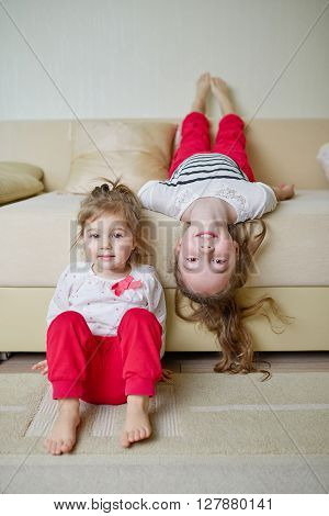 two little cute girls on the couch upside down
