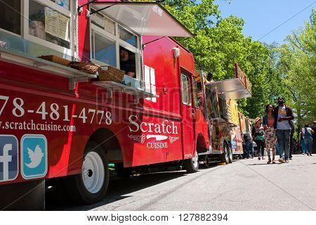 ATLANTA, GA - APRIL 2016: People walk among 30 food trucks lined up in Grant Park at the Food-o-rama festival in Atlanta GA on April 16 2016 .
