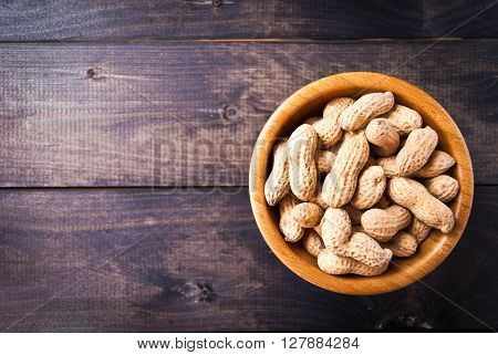 Bowl of fried peanuts with nutshell on wooden background