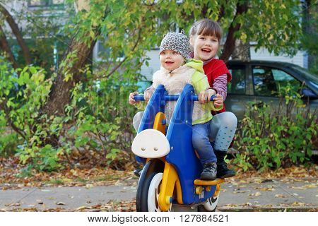 Little girl in red vest and her sister play on wooden motorbike on playground