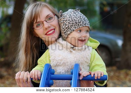 Young smiling woman with little daughter sitting on motorbike on playground at fall