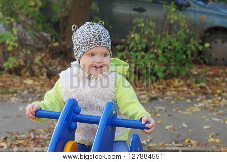 Little pretty girl in vest sits on wooden motorbike on playground at sunny day