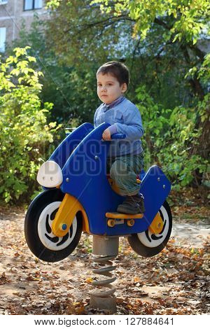 Little handsome boy sits on wooden motorbike on playground at fall