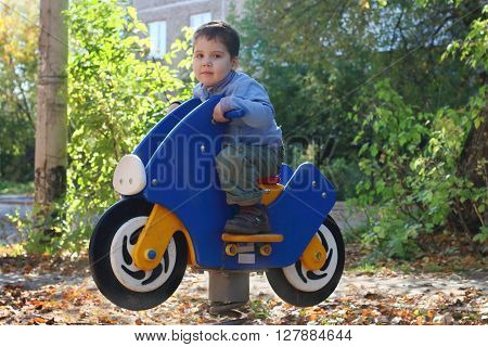 Little handsome boy sits on wooden motorbike on playground at sunny day