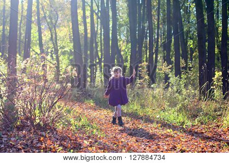 Little beautiful girl in coat runs in park among trees in sunny autumn day