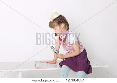 Little girl reading book while sitting at bench holding magnifying glass