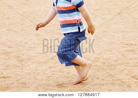 Legs od barefoot of little boy in shorts running on sand at summer