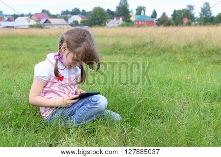 Little girl sits and plays with tablet pc at green meadow near village