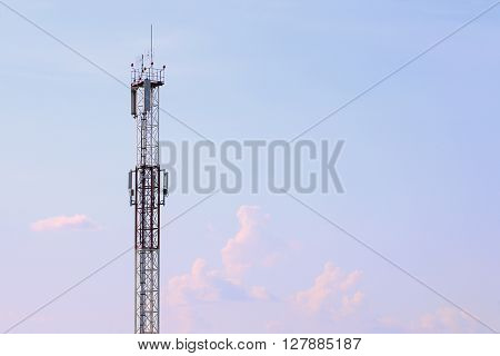 Tall modern cell tower clouds and beautiful sky at summer evening