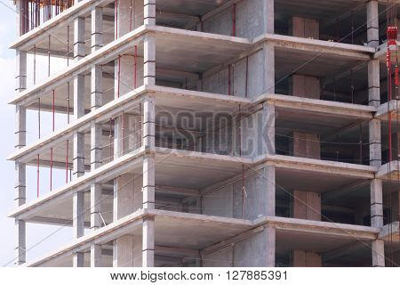 High concrete residential building with skeleton of floors on construction site