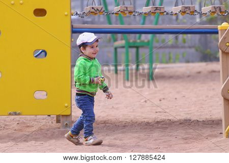 Handsome little boy plays with toy car on children playground at summer