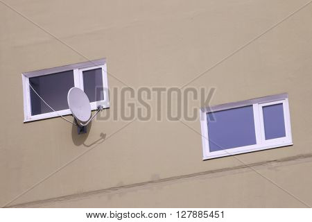Two windows of residential building and white satellite dish at sunny day