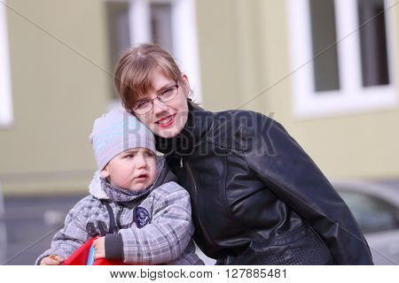 Young mother and her little cute son on playground at sunny spring day
