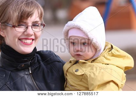 Happy mother and her little cute daughter outdoor at sunny spring day