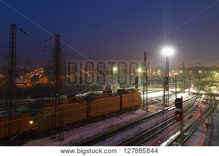 Freight train with carriages move on railways at winter night