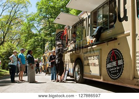 ATLANTA, GA - APRIL 2016: People stand in line to buy meals from a food truck lined up in Grant Park at the Food-o-rama festival in Atlanta GA on April 16 2016 .