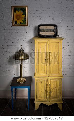 Still Life of vintage yellow cupboard old radio framed painting brass table lamp and vintage small table on dark wooden floor and white bricks wall in Studio