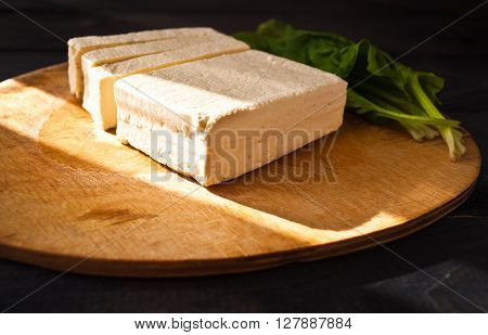 Uncooked tofu slices and green leaves of fresh spinach on cutting board and sunlight from the window