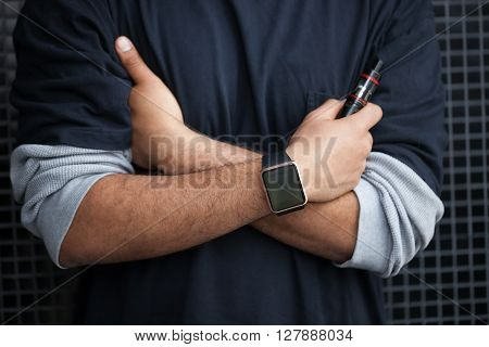 Hands of African model wearing smart wrist watches and holding vaporizer.Modern gadget that lets you always stay connected to internetsocial media from everyware and trendy e-cigarette