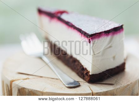 Slice of delicious cheesecake with raspberry on a wooden plate in cafe. Great piece of sweet dessert true delicacy. Close up macro photo