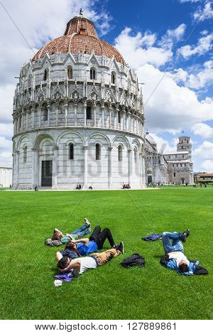 PISA, ITALY, 19th MAY, 2013 Young Guys Chilling on Green Grass Next to Cathedral Monument Piazza dei Miracoli in Pisa Italy