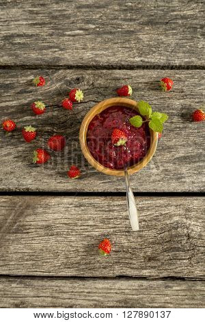 Top view of a bowl of delicious home made strawberry jam or jelly decorated with whole fresh strawberry and mint leaves and ripe strawberries scattered around it.