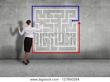 Back view of businesswoman drawing labyrinth on wall