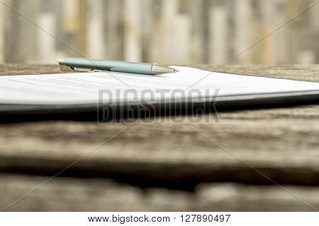 Low angle view of a pen lying on a contract legal paper or document.