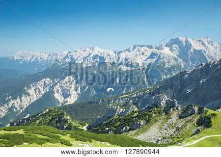 Alps mountains summer aerial view with free soaring paraglider over beautiful Alpine landscape