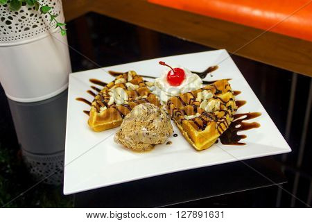 Sweet waffles with chocolate sauce and ice cream chocolate on the table