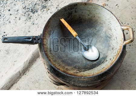 Old metal pan with ladle on the stove for cooking in the outside kitchen of rural house.