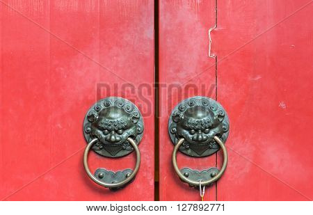 Old brass knocker with lion head in the traditional Chinese style on the temple door.