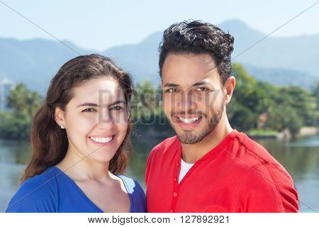 Attractive caucasian couple in vacation looking at camera with sea trees mountains and sky in the background