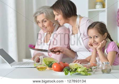 happy women with little girl cooking in kitchen