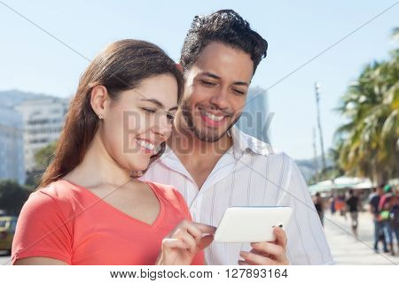 Modern love couple looking photos on cell phone in the city with modern buildings in the background