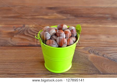 Raw hazelnuts in a small decorative green bucket. Brown wooden table. Macro