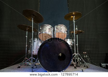 Modern drum set on black stage background prepared for playing. Professional drum kit with some cymbals on stage before a live concert. Drummer, music band, night show, sound recording concept