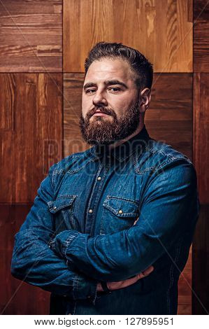Portrait of a serious man with beard on a wooden texture in barbershop. Happy bearded man. Handsome young bearded man keeping arms crossed and smiling while standing.