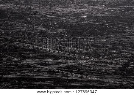 Grunge background with black paint brush marks and scratches.