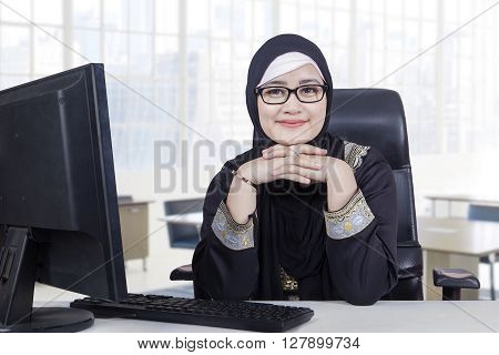 Portrait of Arabic young woman working in the office while wearing headscarf and smiling at the camera