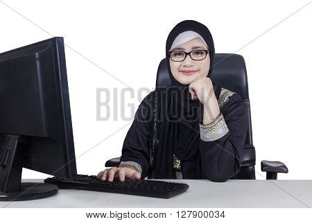 Pretty Arabic businesswoman wearing headscarf and smiling at the camera with computer on the table