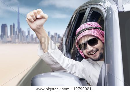 Image of successful Arabic person driving a car while raising his hand and wearing sun glasses