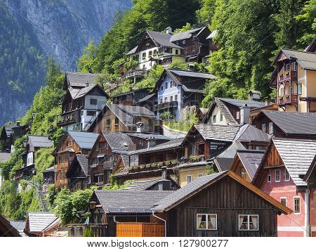Scenic picture-postcard view of traditional old wooden houses up the hill in famous Hallstatt mountain village morning summer