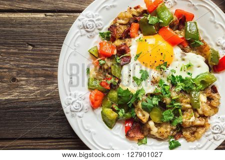 Fried egg with pepper bacon potatoes and cilantro on rustic wooden background. Top view.