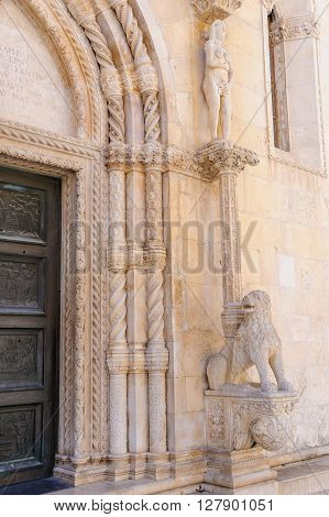 Eve standing on a lion next to the north side portal of St. James cathedral